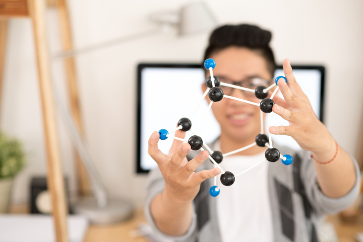 Chemistry student with model of molecules