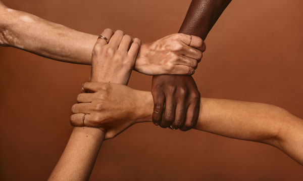 Multi-ethnic hands holding each other in a circle