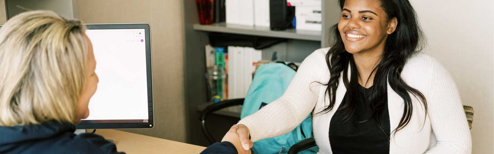 a graphic depicting person on a computer with headphones