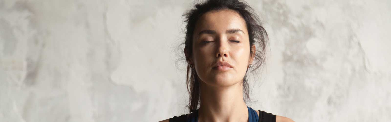 woman's face with closed eyes practicing yoga stock photo