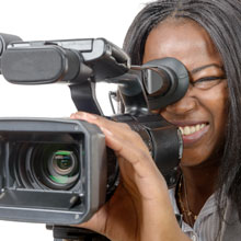 A Black female filmmaker working with her camera