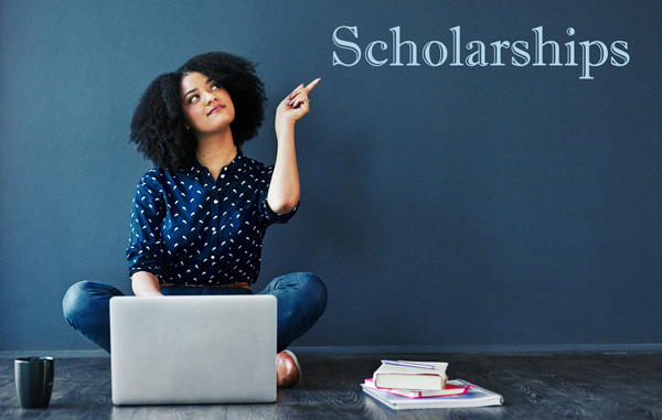 female student pointing to letters spelling out the word scholarships
