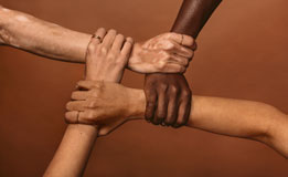 multi-racial hands held together in a circle